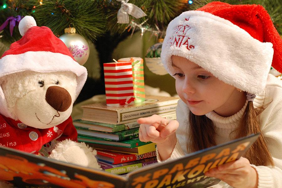 Nicolausserivice – Kind liest ein Buch mit einem Kuschelbär